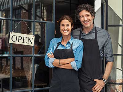 business woman and business man with open sign