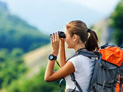 woman using binoculars on hike