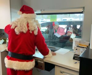 Santa at drive up with children.